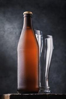 Bottiglia di birra chiara e due bicchieri vuoti su un tavolo di legno