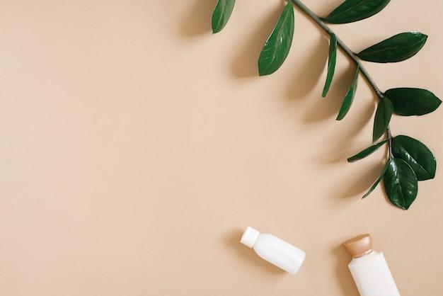 Una bottiglia di sapone liquido o gel doccia su fondo beige con un ramo della pianta