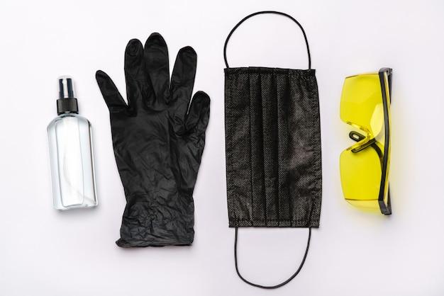 Bottiglia di lozione, disinfettante o sapone liquido, occhiali protettivi occhiali e maschera protettiva isolato sul muro bianco con tracciato di ritaglio.