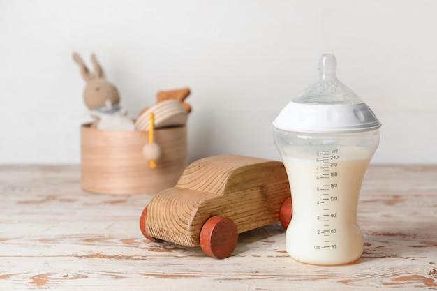 Bottiglia di latte per bambini con giocattoli sul tavolo