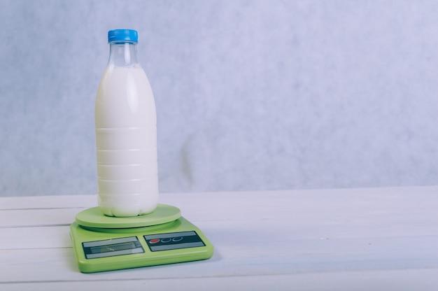 Una bottiglia di latte su una bilancia da cucina su un tavolo di legno.