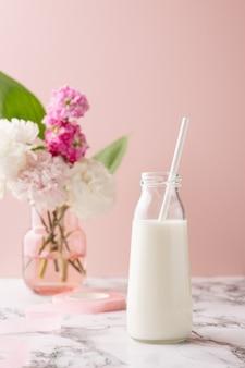Una bottiglia di latte su un tavolo di marmo su sfondo rosa con bouquet di fiori rosa e bianchi, composizione di bevande luminose e pastello verticale