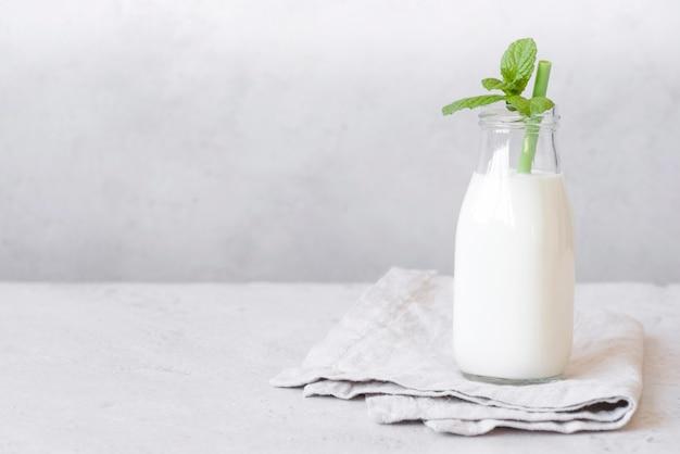 Bottiglia di latte e foglie di menta piperita