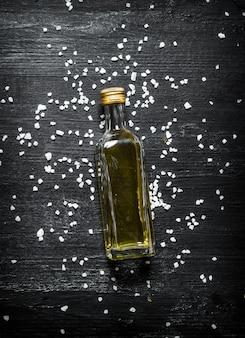 Bottiglia di olio d'oliva. su fondo rustico nero.