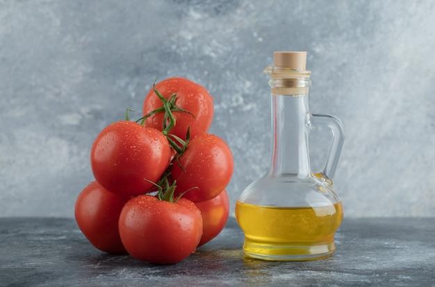 Bottiglia di olio d'oliva con pomodori rossi su superficie in pietra