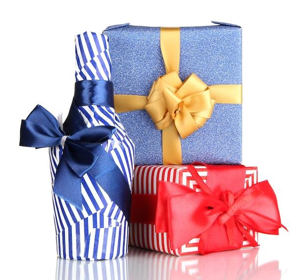 Bottiglia confezionata in carta regalo con regali isolati su bianco