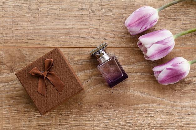 Bottiglia di profumo e confezione regalo marrone su assi di legno con tulipani lilla.