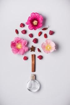 Bottiglia di profumo e ingredienti della fragranza: fiori, bacche e spezie. concetto di fragranza del profumo