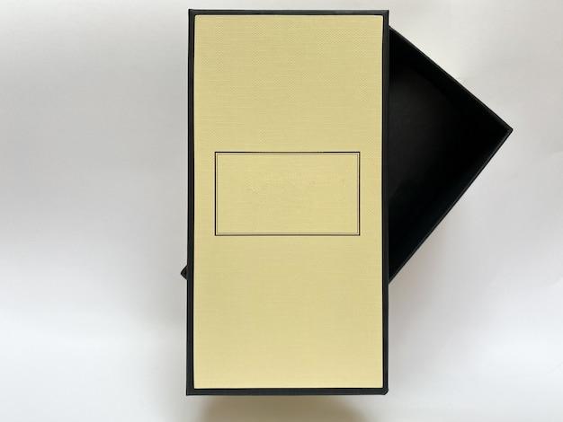 Una bottiglia di profumo da una scatola gialla su uno sfondo bianco isolato