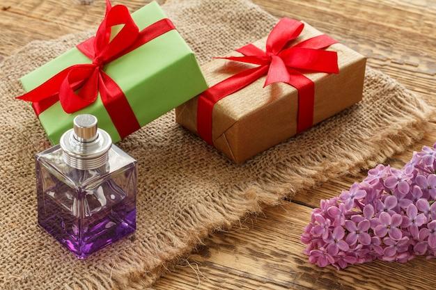 Bottiglia di profumo, scatole regalo e fiori lilla su tela di sacco e assi di legno