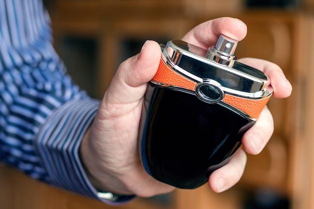 Bottiglia di profumo in mano d'uomo