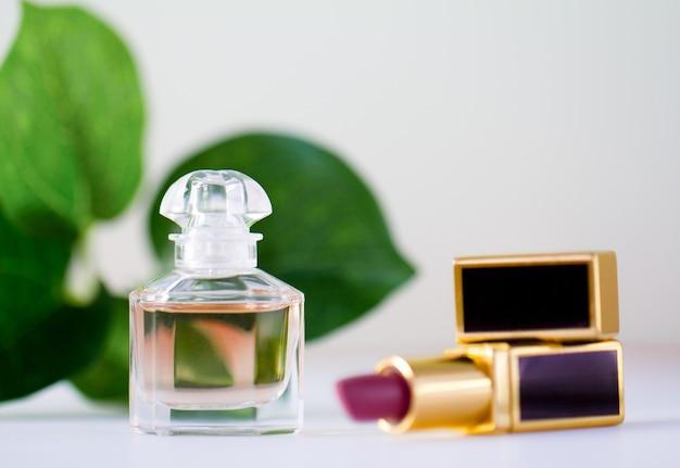 Una bottiglia di profumo e rossetto rosa su una delle foglie verdi.