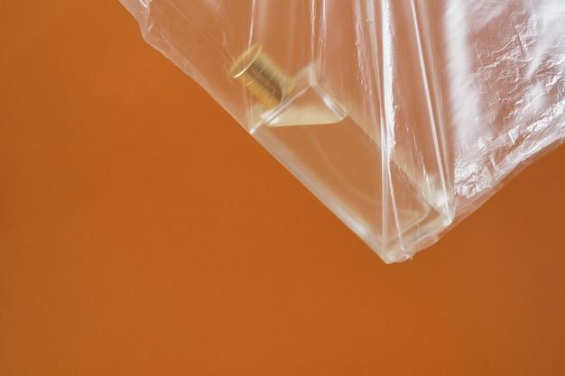 Bottiglia di profumo in un sacchetto di plastica su uno sfondo marrone, idea originale, spazio copia ecologico e nessun concetto di plastica