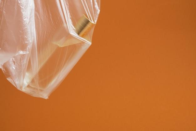 Bottiglia di profumo in un sacchetto di plastica su fondo marrone, idea originale, spazio copia