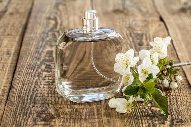 Bottiglia di profumo con ramo di bellissimi fiori di gelsomino sullo sfondo di legno. concetto di fare un regalo nei giorni festivi.