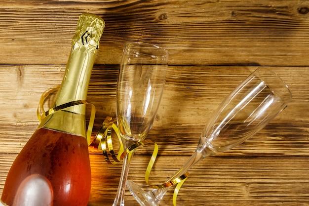 Bottiglia di spumante rosa e due bicchieri di champagne vuoti su fondo di legno. vista dall'alto