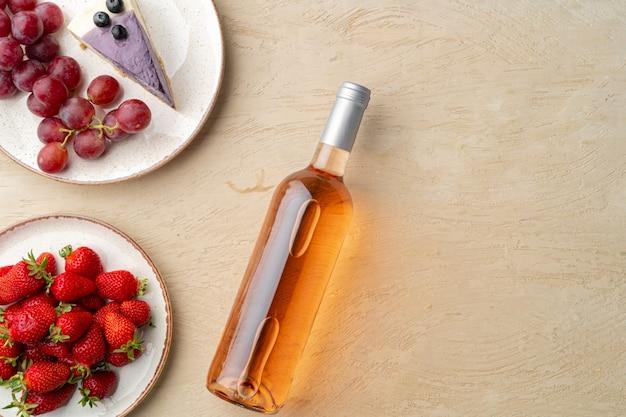 Bottiglia di vino rosa, frutta e pezzo di cheesecake su sfondo grigio piatto vista dall'alto