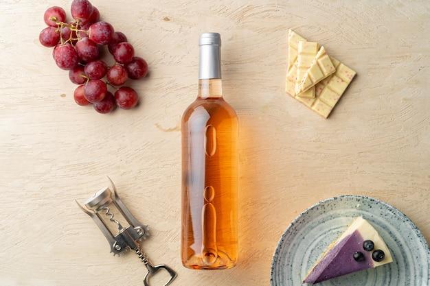 Bottiglia di vino rosa, frutta e pezzo di cheesecake sul piatto grigio laici