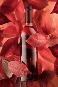 Una bottiglia di vino rosato rosso sullo sfondo delle foglie di autunno. umore autunnale e relax.