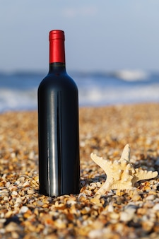 Bottiglia di vino rosso sul primo piano della spiaggia