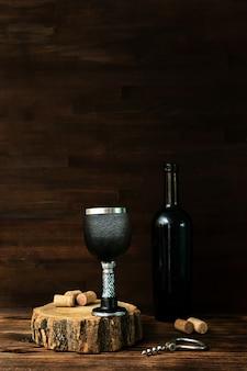 Bottiglia di vino rosso e vetro nero, cavatappi e sugheri sulla tavola di legno, fondo scuro della bevanda della bevanda dell'alcool, natura morta.