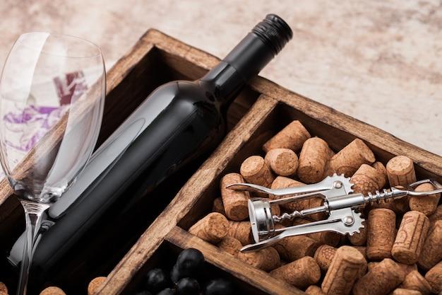 Bottiglia di vino rosso, tappi e uva in una scatola di legno
