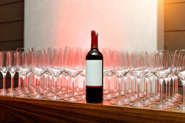 Bottiglia di vino rosso su catering per eventi, molti bicchieri di vino vuoti