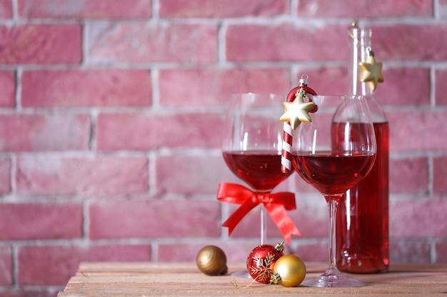 Bottiglia di vino rosso e bicchieri con regali di natale sulla superficie della parete