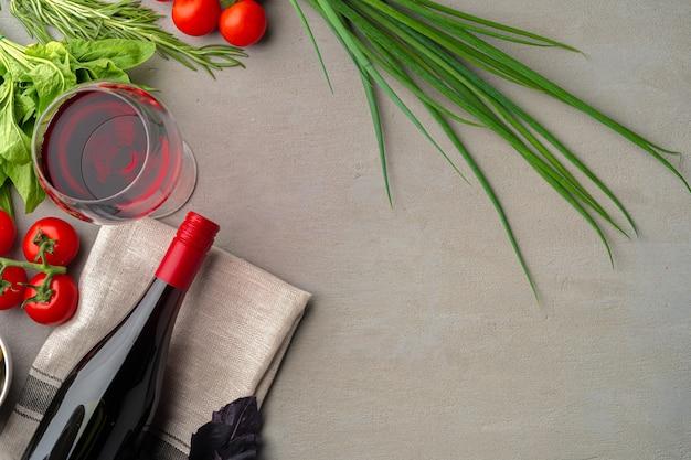 Bottiglia di vino rosso su superficie grigia con verdure