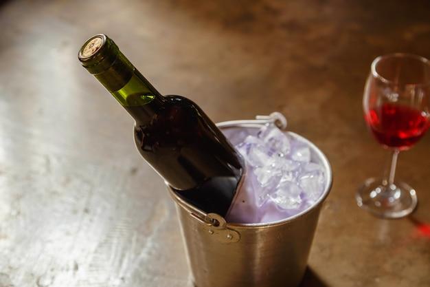 Bottiglia di vino rosso in un secchiello del ghiaccio e un bicchiere di vino rosso