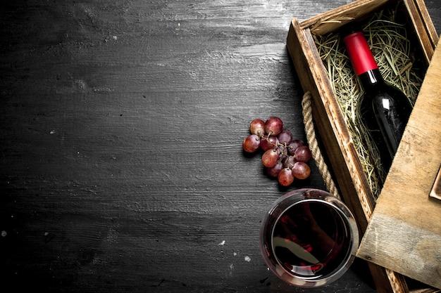Bottiglia di vino rosso in una vecchia scatola con un ramo di uva sulla lavagna nera