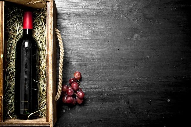 Bottiglia di vino rosso in una vecchia scatola con un ramo d'uva. sulla lavagna nera.