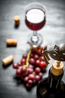 Bottiglia di vino rosso con un cavatappi su uno sfondo di legno nero