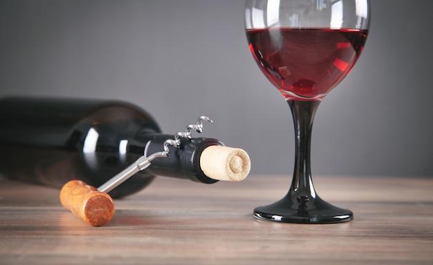 Bottiglia di vino rosso con bicchiere e cavatappi.