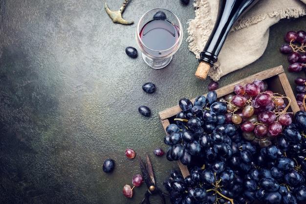 Una bottiglia di vino rosso con vetro e uva su pietra scura