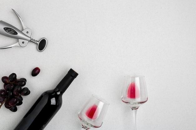 Bottiglia di vino rosso con bicchieri su sfondo bianco vista dall'alto mockup