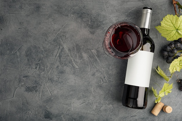 Bottiglia di vino rosso con etichetta. bicchiere di vino e uva. modello di bottiglia di vino. vista dall'alto.