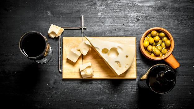 Bottiglia di vino rosso con una fetta di formaggio e sulla tavola. su uno sfondo di legno nero.
