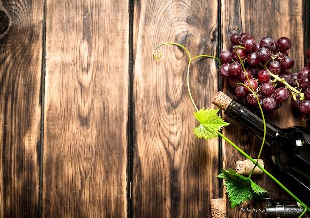 Bottiglia di vino rosso con un rametto d'uva. su un tavolo di legno.