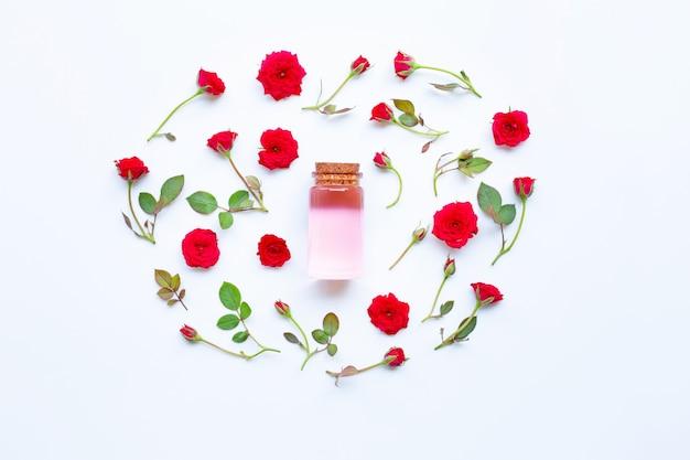 Bottiglia di olio essenziale di rosa per aromaterapia su bianco.