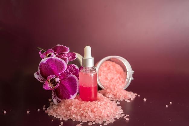 Bottiglia di olio essenziale di rosa, sale da bagno e phalaenopsis su fondo vinoso. foto di alta qualità