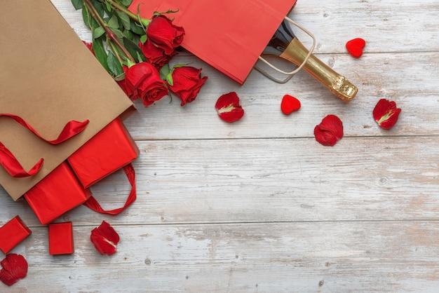 Una bottiglia di spumante borsa artigianale con regali rose di lusso una superficie in legno