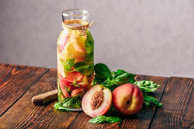 Bottiglia di acqua estiva con pesche a fette e foglie di basilico. coltello e ingredienti sulla tavola di legno.