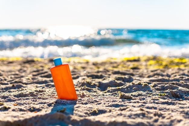 Bottiglia di crema solare protectionnd bottiglia di crema bianca sulla sabbia vicino al mare. protezione solare e pigmentazione della pelle