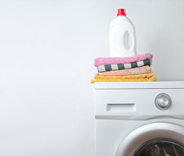 Bottiglia di gel di lavaggio e pila di asciugamani sulla lavatrice