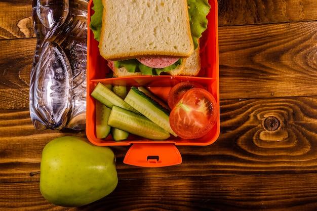 Bottiglia d'acqua, mela verde e scatola per il pranzo con panino, cetrioli e pomodori su tavola in legno rustico. vista dall'alto