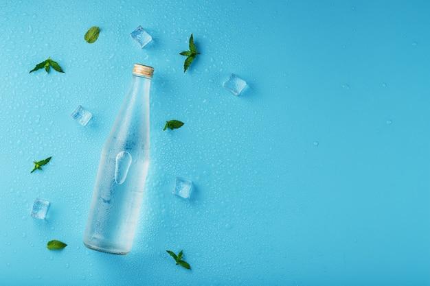 Bottiglia d'acqua con cubetti di ghiaccio e foglie di menta