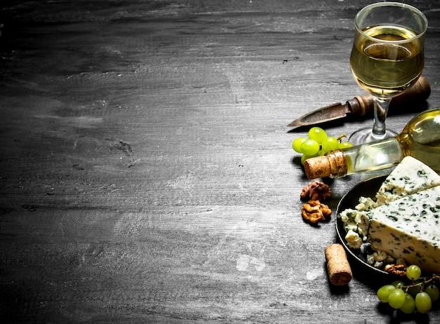 Bottiglia di vino bianco con una fetta di formaggio con muffa blu. su un tavolo di legno nero.