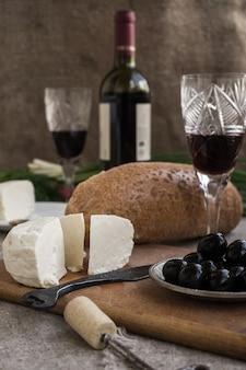 Bottiglia di vino, formaggio e pane bianco sono sul saccheggio