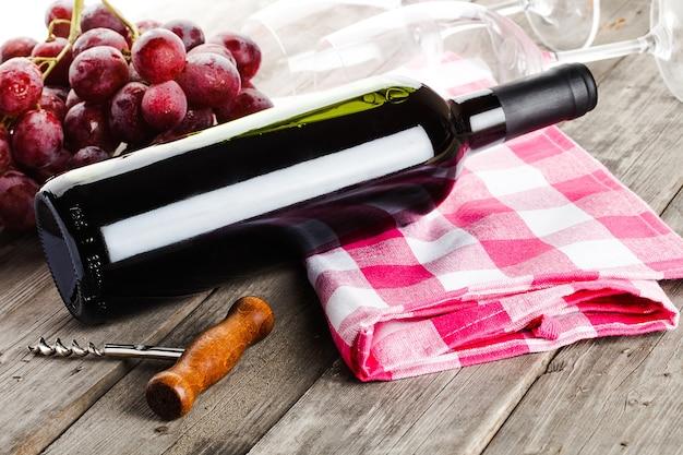 Bottiglia di vino cavatappi amd uva sulla tavola di legno